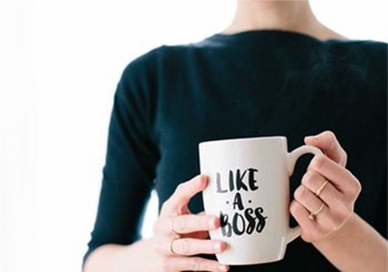 Woman's hands, holding a mug with 'like a boss' written on it in handwriting script