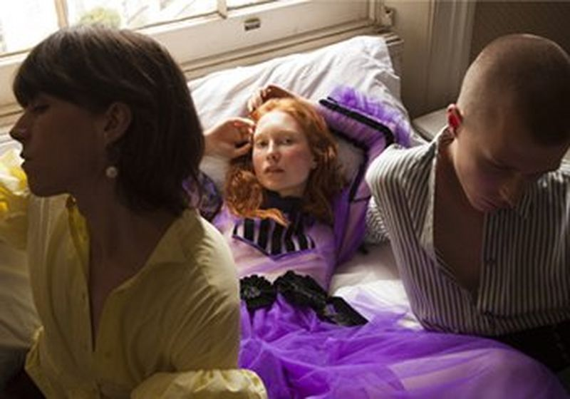 Two people sat on a bed with a redheaded woman lying between them