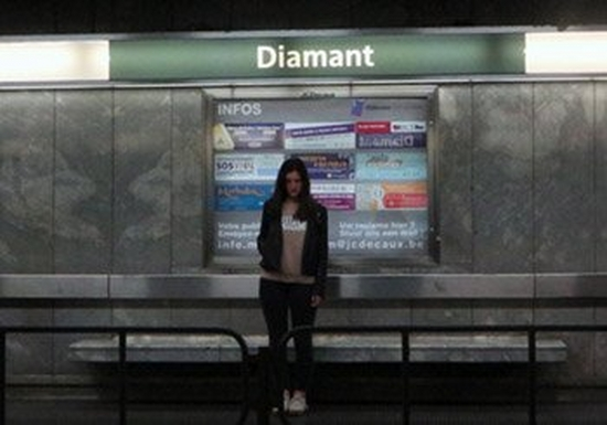 A young woman stands alone on a deserted metro platform.
