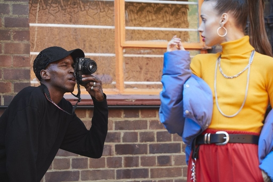 Photographer Ejiro Dafé photographs a woman in bright clothing with a Canon EOS R6 and a Canon RF 50mm F1.8 STM lens.