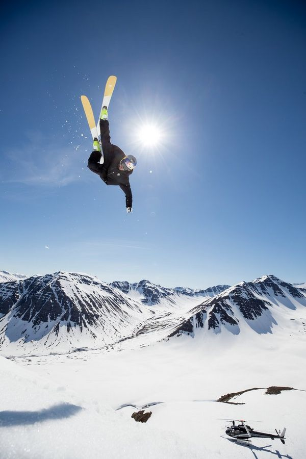A snowboarder upside-down in the air with a helicopter in the background. Photo by Richard Walch.
