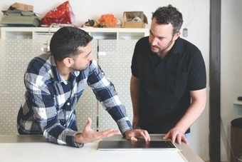 Two men discuss printed material they are looking at on a desk
