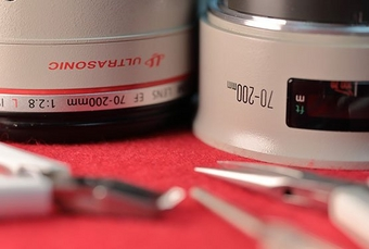 A Canon L lens with tools sitting on a repair table