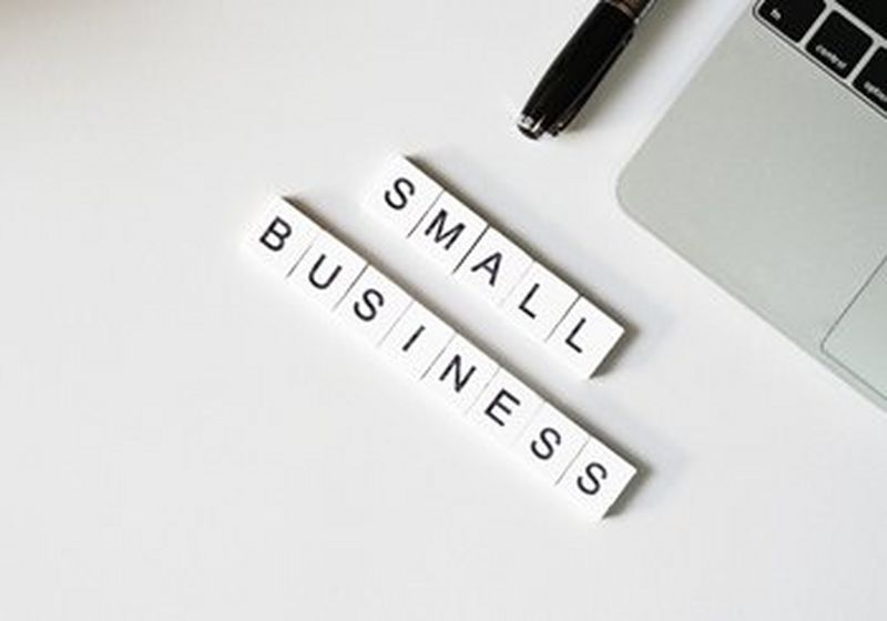 'SMALL BUSINESS' spelled out in tiles on a desk next to a keyboard and pen.