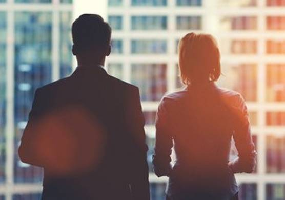 A man and woman, dressed in office attire and standing with their backs to the camera, looking out of a window at other office buildings.