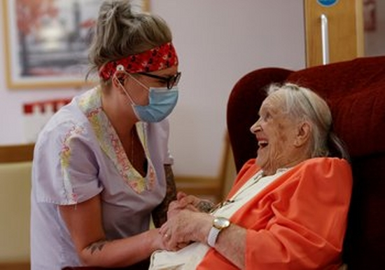 A woman in a medical mask and overalls holds the hands of a smiling elderly woman who wears an orange cardigan.
