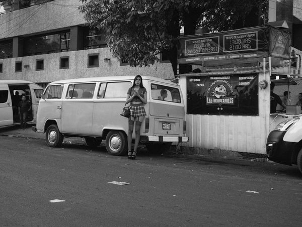 A young woman stands by parked cars on a street.