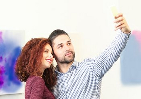 A couple take a selfie in front of a piece of modern art