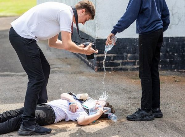 A schoolgirl lies on the floor having water poured over her face