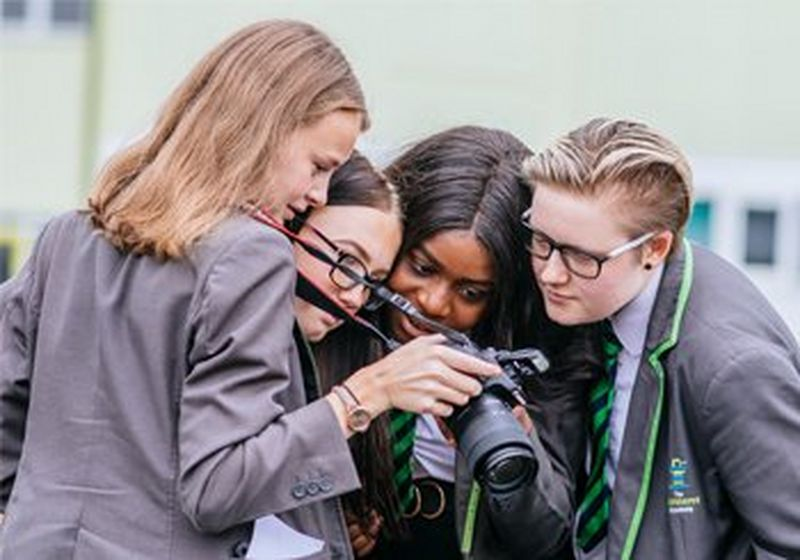 Four students in school uniform look at the rear display on a Canon camera