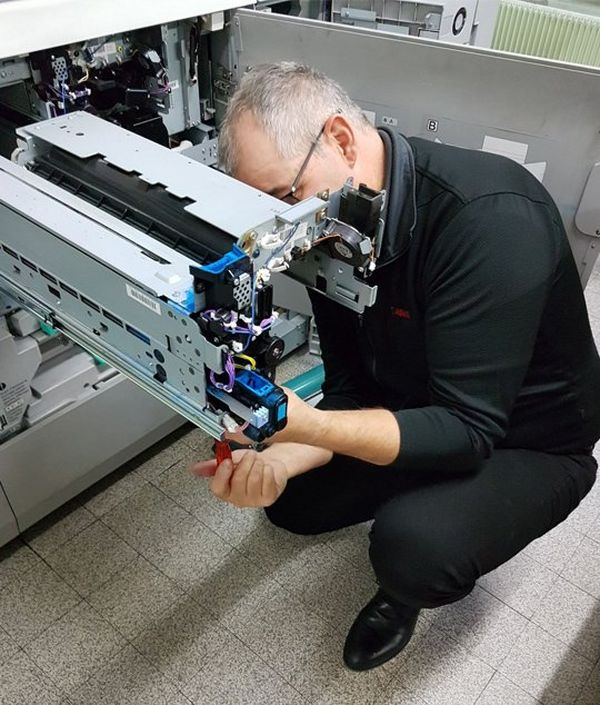 A Canon service engineer fixes the inside of a printer.