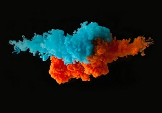Bright blue and orange ink against a black background, exploding as though in water.