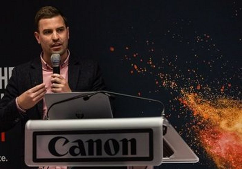 Sam Tatam, giving his keynote speech at a Canon launch event, holding a microphone and standing behind a Canon branded lectern