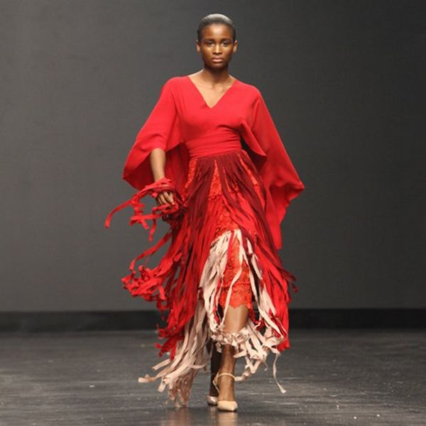 A model in red walks down the runway