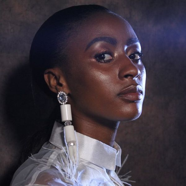 A head and shoulder shot of a model dressed in white with white drop earrings