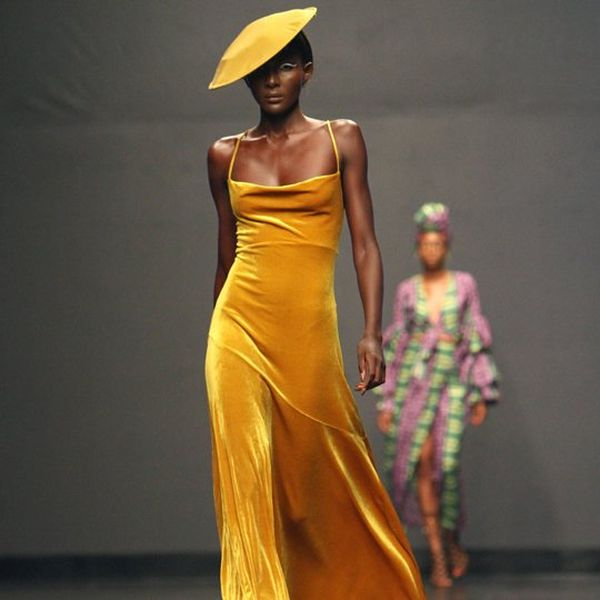 A model on a catwalk wearing a mustard yellow slip dress and hat