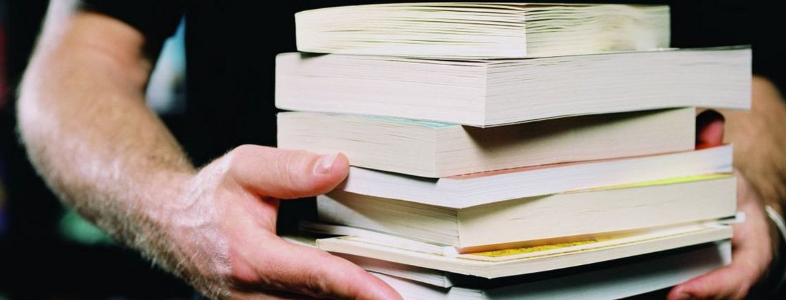 Man holding pile of books with two hands