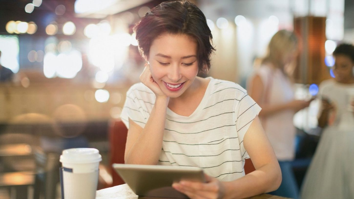 Girl sat at table with coffee reading on tablet