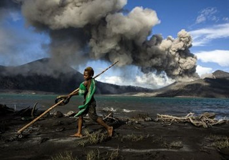 A boy stands, playing, on a grey ash beach by the sea, in the background a volcano is erupting against a blue sky. © Ulla Lohmann