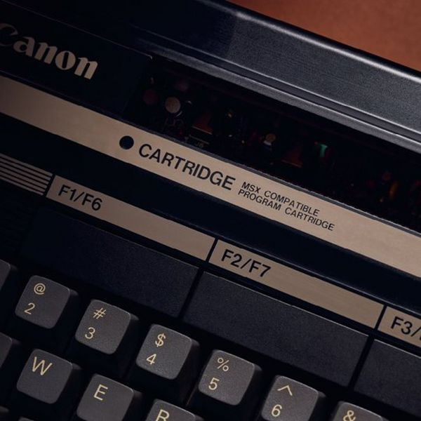 A close up of the Canon V-20 home computer, showing the Canon logo, the text 'CARTRIDGE MSX COMPATIBLE PROGRAM CARTRIDGE' and F keys.