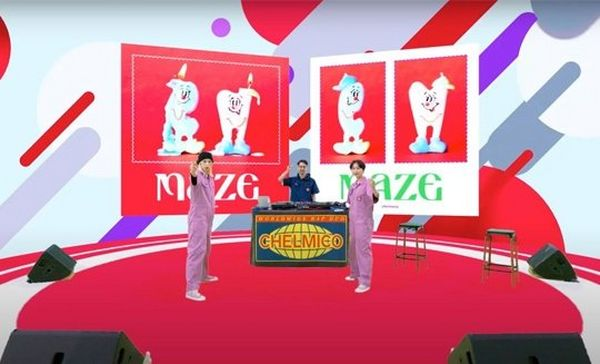 The two women in lilac jumpsuits now stand in the same position in the same studio, but with red, grey and purple patterns on the wall behind them, and two banners with the word 'maze' on them. © Warner Music Japan Inc.