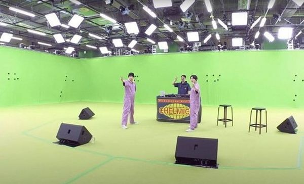 Two women in lilac jumpsuits stand in a green-screened studio. They each have an arm outstretched. Behind them is a man standing behind a DJ booth that is labelled 'chelmico'. © Warner Music Japan Inc.