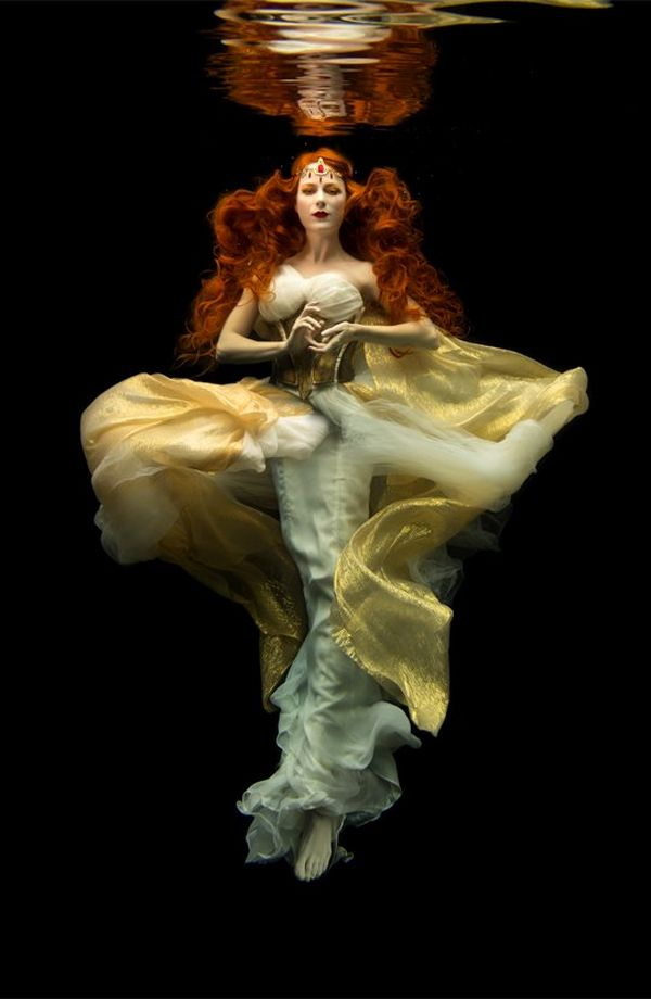 A red-haired woman floats against a black background, wearing a diaphanous dress of gold and pale yellow.