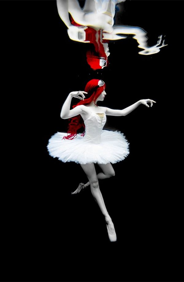 A ballet dancer with pillar-box red hair and alabaster skin, floats en pointe against a black background, wearing a pure white tutu.