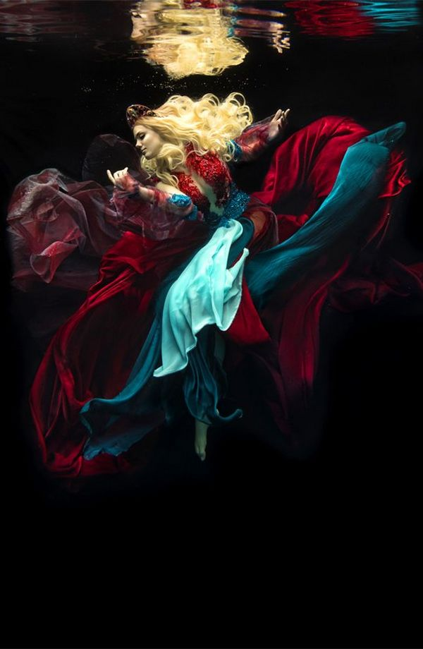 A golden-haired woman in a many-layered gown of blood red and sea blues, floats against a black background.