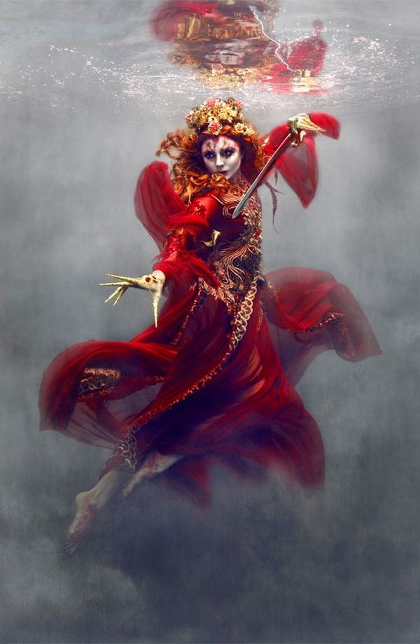 A woman with a painted face floats in clouds and wears an eastern-style red gown with a semi-mandarin collar. Her red hair is decorated with flowers and she assumes the battle position, directing a sword at an unknown opponent to the left-hand side of the image.
