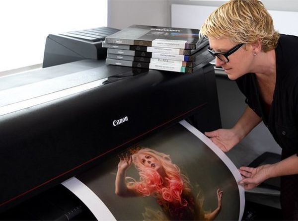 Cheryl stands to the right, with short, blonde hair and black framed glasses. She gently holds a print as it emerges from a Canon PRO-4100 printer.