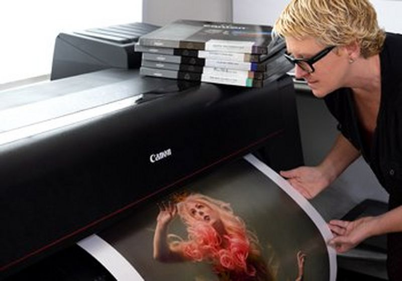 Cheryl stands to the right, with short, blonde hair and black framed glasses. She gently holds a print as it emerges from a Canon PRO-4000 printer.