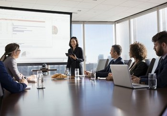 A woman holding a tablet gives a presentation in front of a projector screen for five colleagues, who are sat at a boardroom table with laptops, glasses of water and a plate of croissants.