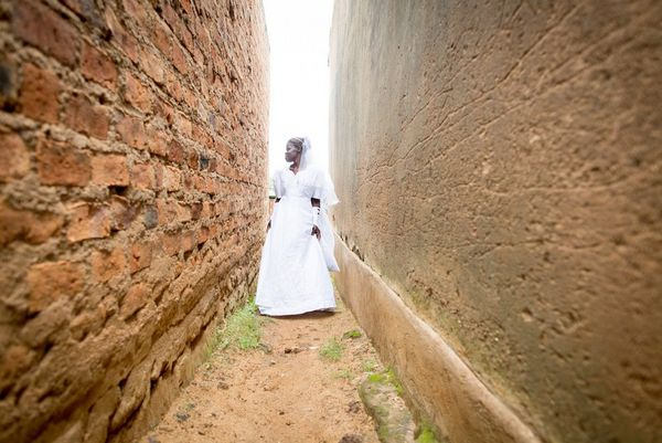 A smiling bride in Kenya, wearing her wedding dress, is photographed in an alley between red brick walls.