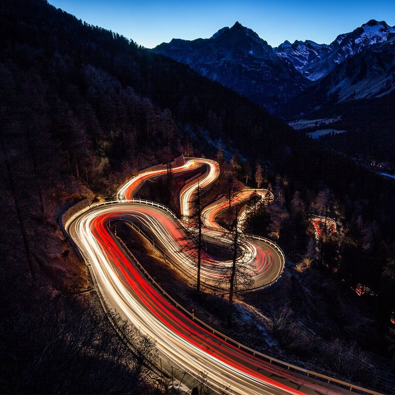 Winding mountain road lit up brightly