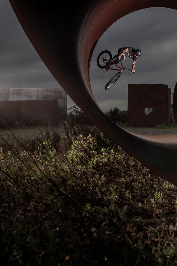 A BMX rider jumping off the inside of a large tube.