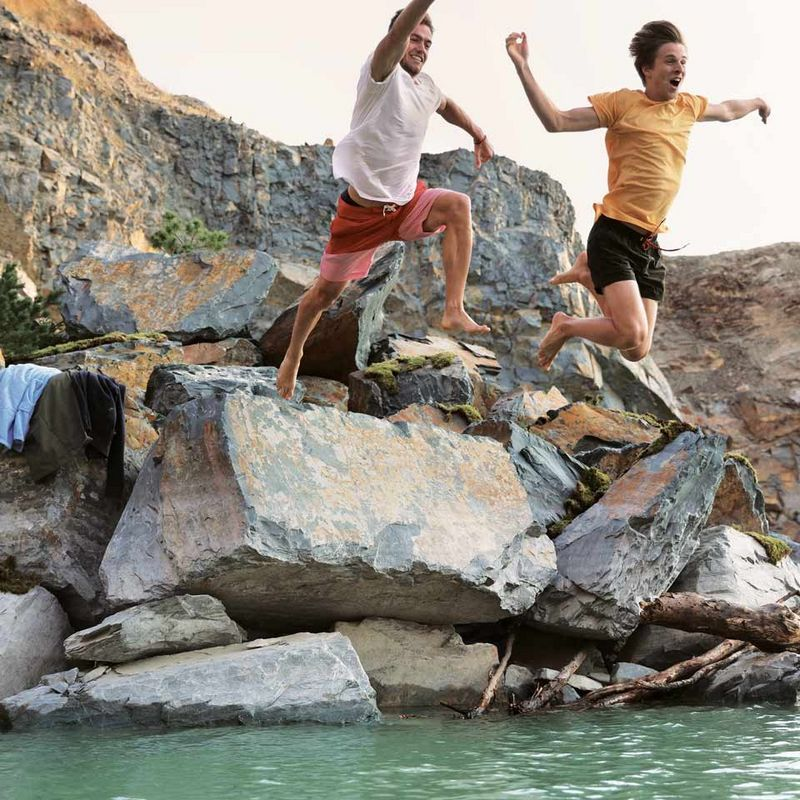 Two friends jumping off rocks into cold lake