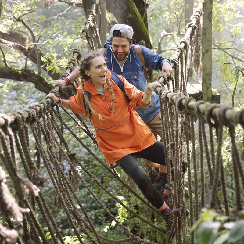 Couple stepping onto rope bridge in jungle adventure