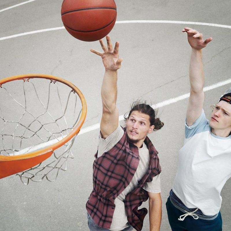 Two friends playing basketball in driveway