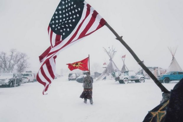 Veterans carry an American and a Mohawk Warrior Society flag through the storm.