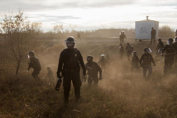 Riot police clear marchers from a secondary road outside a Dakota Access Pipeline (DAPL) worker camp using rubber bullets, pepper spray, Tasers and arrests.
