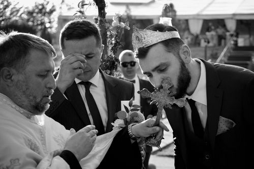 Behind the scenes at Romanian wedding - Groom kissing Cross - taken with a EOS 5D Mark IV