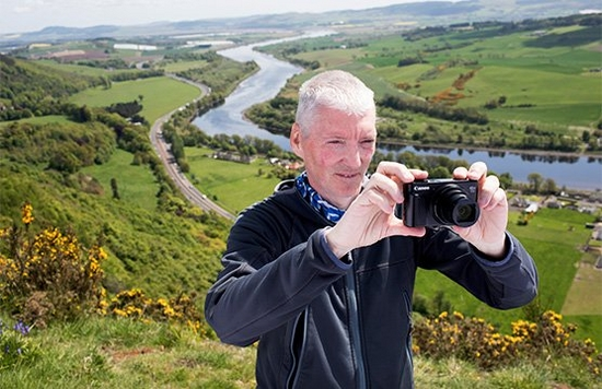 Alan Rowan stands on the side of a hill taking a photo using a Canon compact camera, with a river in the valley behind him.