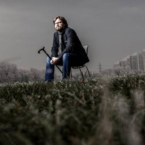 man sitting on chair in a field