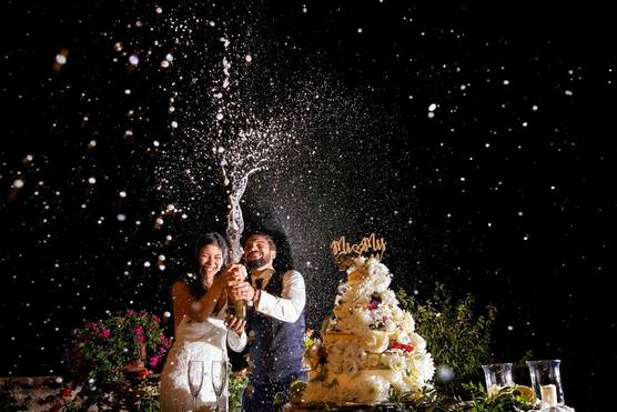 A spurt of champagne frozen in the air as smiling newlyweds celebrate next to a towering cake at their wedding reception.