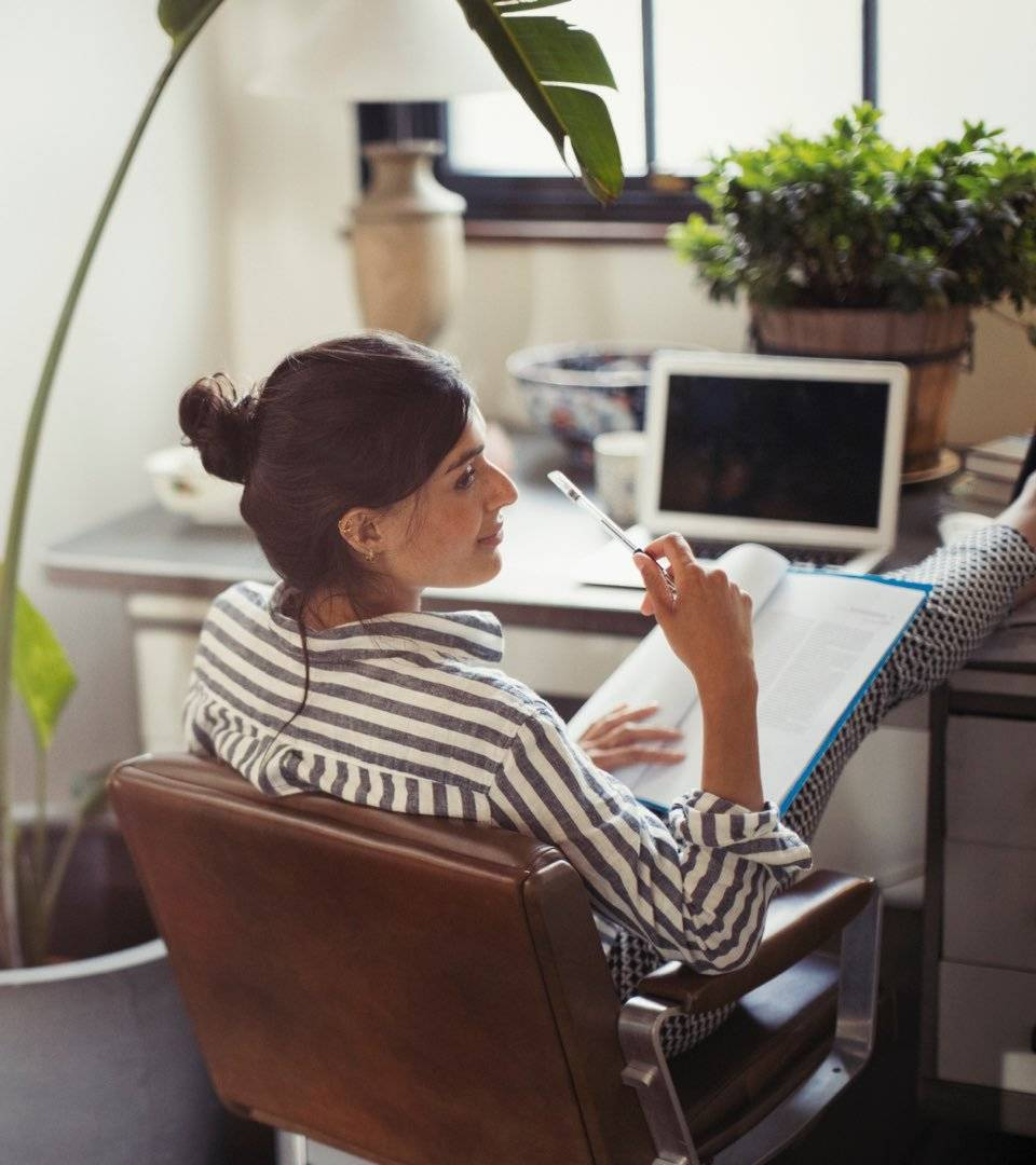 Women in stripy shirt sits in a brown leather chair while resting her legs on the desk beside a laptop as she reads a document.