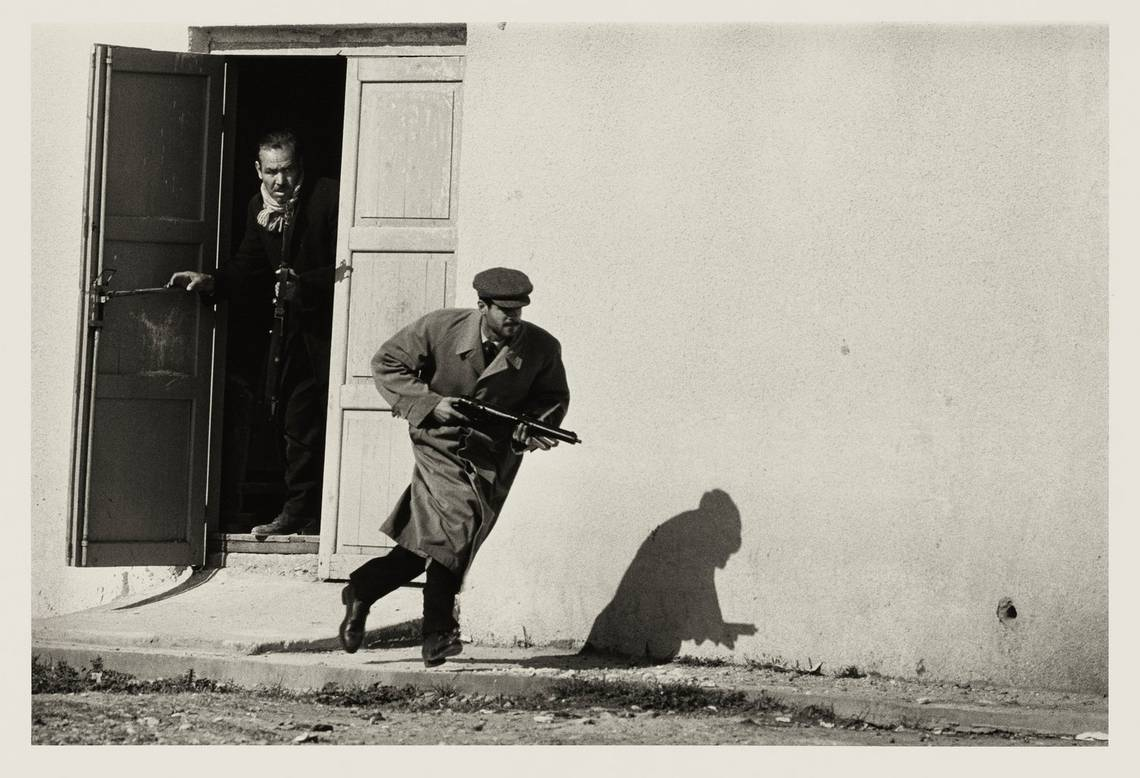 A Turkish Cypriot bursts out of the side-door of a cinema clutching a gun, in the middle of the Cyprus Civil War.