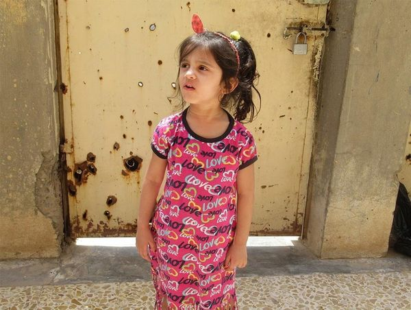 Maryam Raheem Jassem's younger sister in pink dress with 'love' printed across it.
