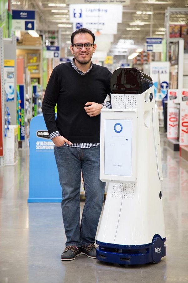 Marco Mascorro standing next to the robot he created.