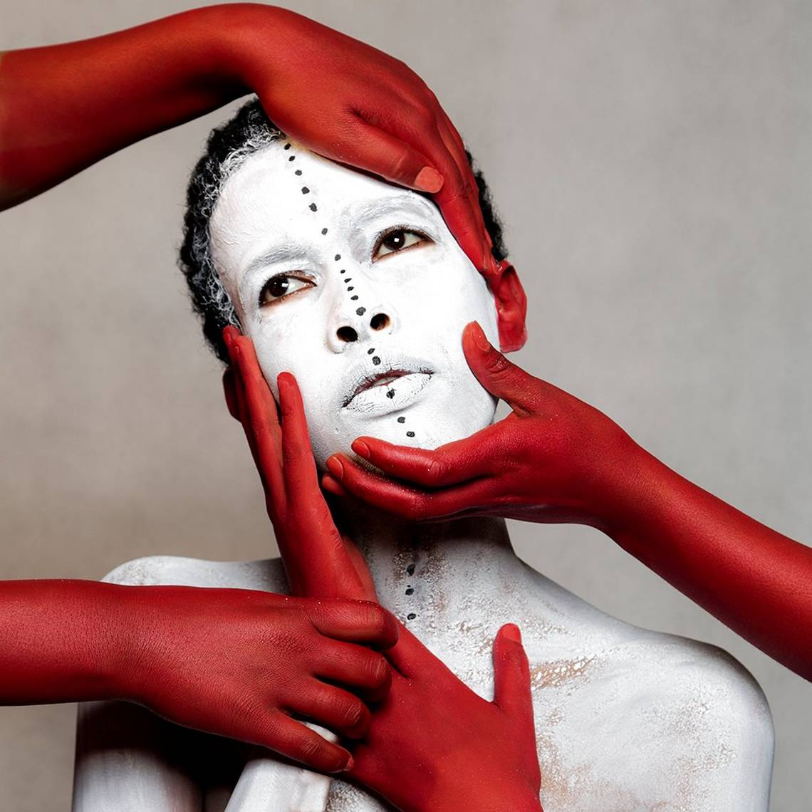 A head-and-shoulders shot of a woman in white body paint, with red painted hands holding her face. Taken by Aïda Muluneh on a Canon EOS 5D Mark III.